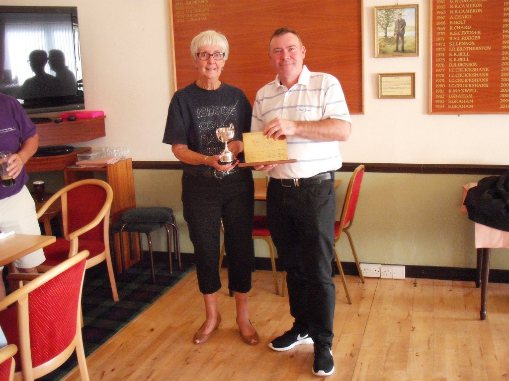 Mr Alistair Water of the Tiree team accepts the Oban Times Cup and the Coll-Tiree plaque from Mrs Margaret Thorburn